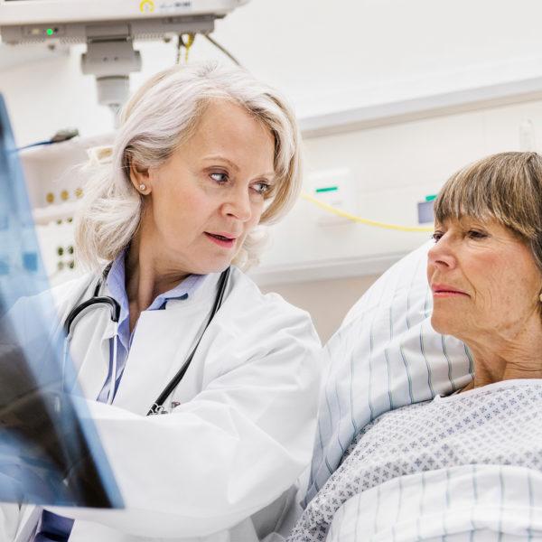 Me´dica a falar com uma doente e com um raio x na mão