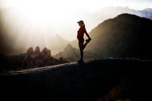 Mulher desportista com uma linda paisagem de fundo a fazer aquecimento