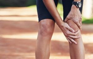 Mulher com as duas mãos a segurar a rótulo devido às dores