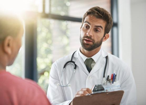Médico a conversar com um doente segurando uma placa na mão