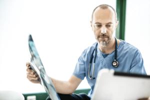 Médico pensativo a analisar um raio x num tablet